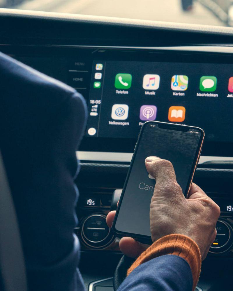 Blick auf das Cockpit Display und eine Hand die die Connect App bedient.