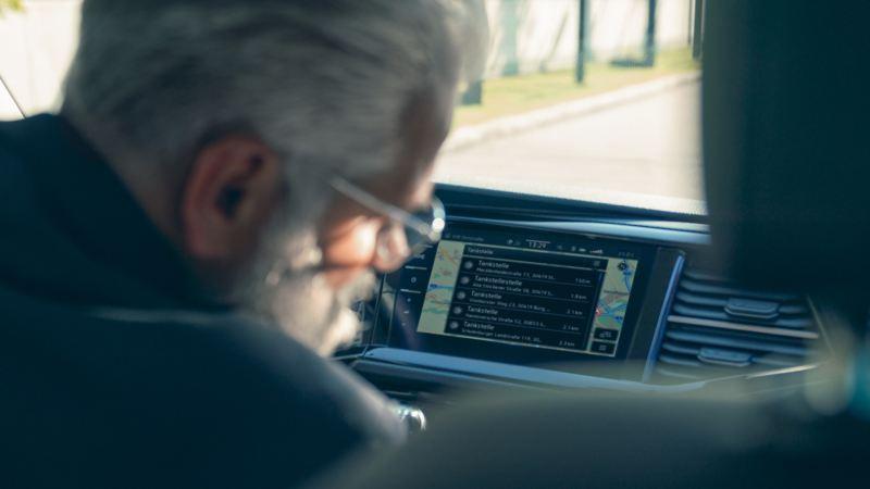 Un homme devant l'écran d'un système de navigation dans un véhicule