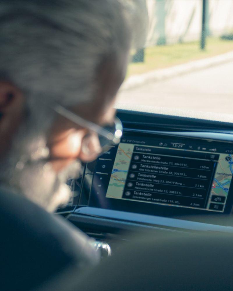 Man sitter i en VW Transportbil med ett infotainmentsystem i bakgrunden