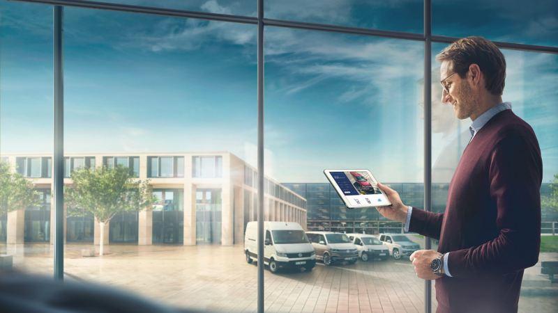 Ein Mann hält ein iPad in der Hand, im Hintergrund stehen verschiedene Volkswagen Nutzfahrzeuge.