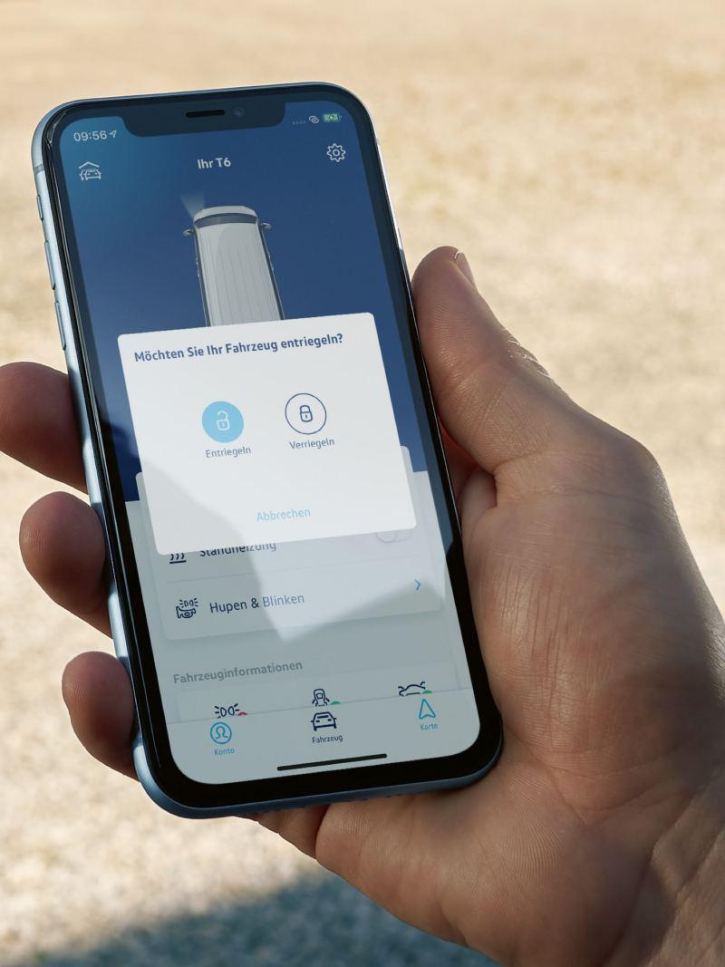 Eine Hand hält ein Smartphone auf dem die We Connect App für Türen und Fenster geöffnet ist.