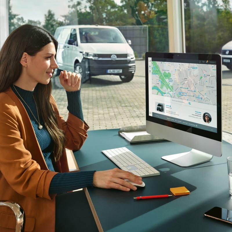 Eine Frau arbeitet an einem PC und benutzt die We Connect Fleet App.