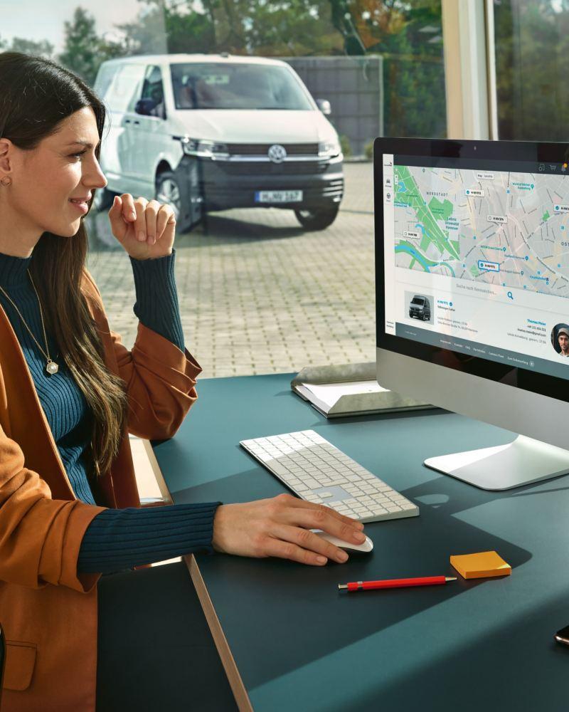 Ein Frau arbeitet an einem PC und hat die We Connect Fleet App offen.