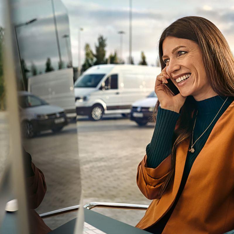 Una donna con un computer sta parlando al telefono in un parcheggio, alle sue spalle dei veicoli commerciali Volkswagen.