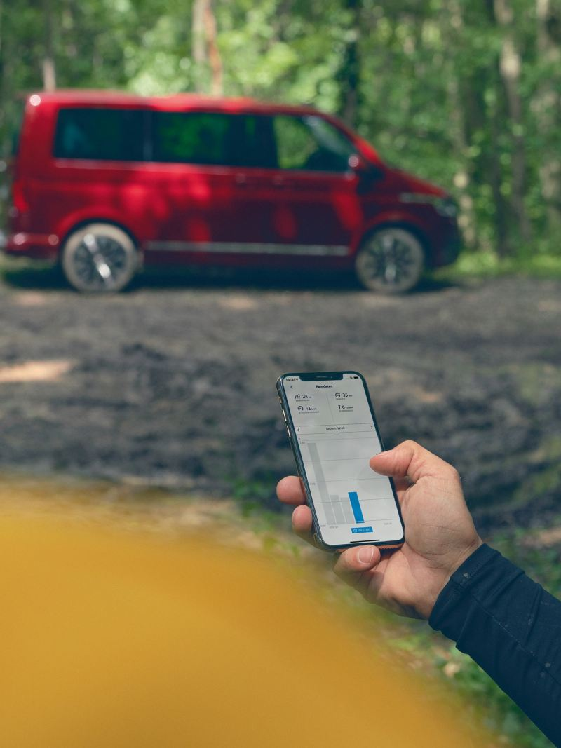 Ein Mann überprüft mit seinem Smartphone die Konfiguration seines Fahrzeugs.