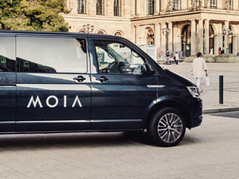 Ein schwarzer MOIA T6 Bus fährt durch eine Stadt.