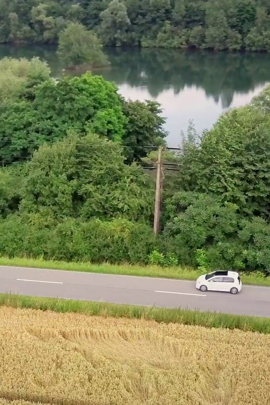 The e-up! drives on a road beside a river