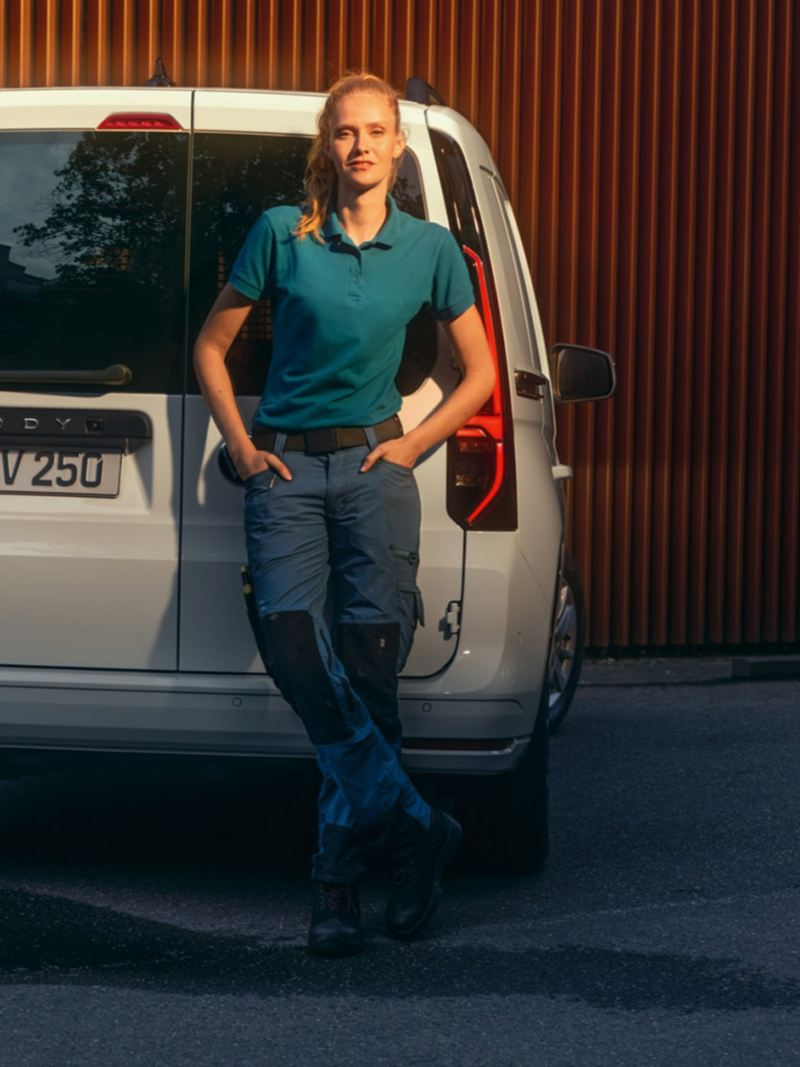 Une femme s'adosse contre une des portes battantes de la nouvelle Volkswagen Caddy Cargo.