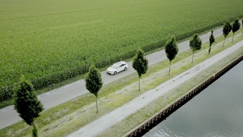 An e-Golf drives on a road beside a canal