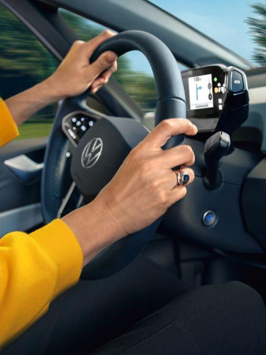 Beifahreransicht einer Person in einem gelben Sweatshirt am Steuer eines Volkswagen ID.3