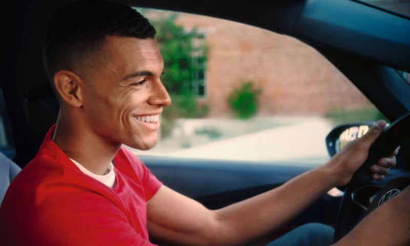 Beifahreransicht eines lächelnden jungen Mannes in einem roten T-Shirt am Steuer eines Volkswagen ID.3