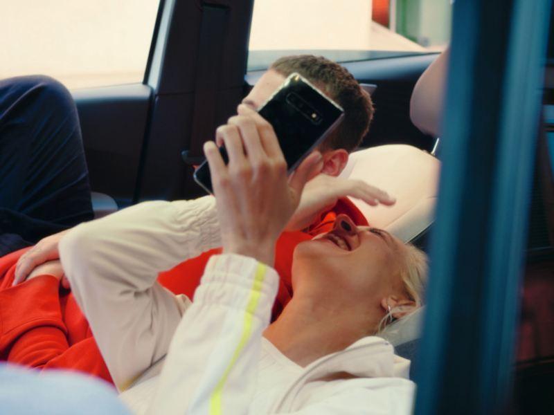 Ein junges Pärchen sitzt mit zurückgeklappten Sitzen lachend in einem Volkswagen ID.3