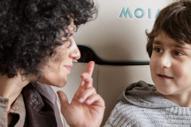 Eine Mutter und ihr kleiner Sohn sitzen in einem MOIA Fahrzeug. Auf der Rückenlehne ist der Schriftzug MOIA eingestickt.