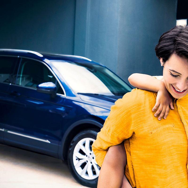 Una madre che porta sulle spalle una bambina passa davanti a una Volkswagen auto