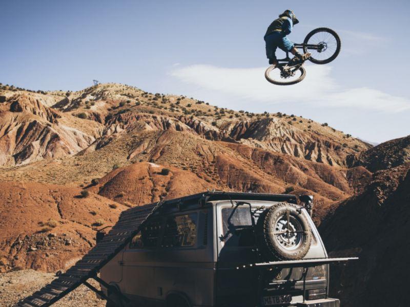 Rob Heran macht einen spektakulären Sprung mit dem Mountainbike – über seinen T3 Bus hinweg.