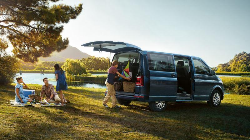 Eine Familie macht Picknick neben einem Multivan
