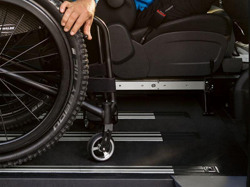 Ein Hand sichert einen Rollstuhl.