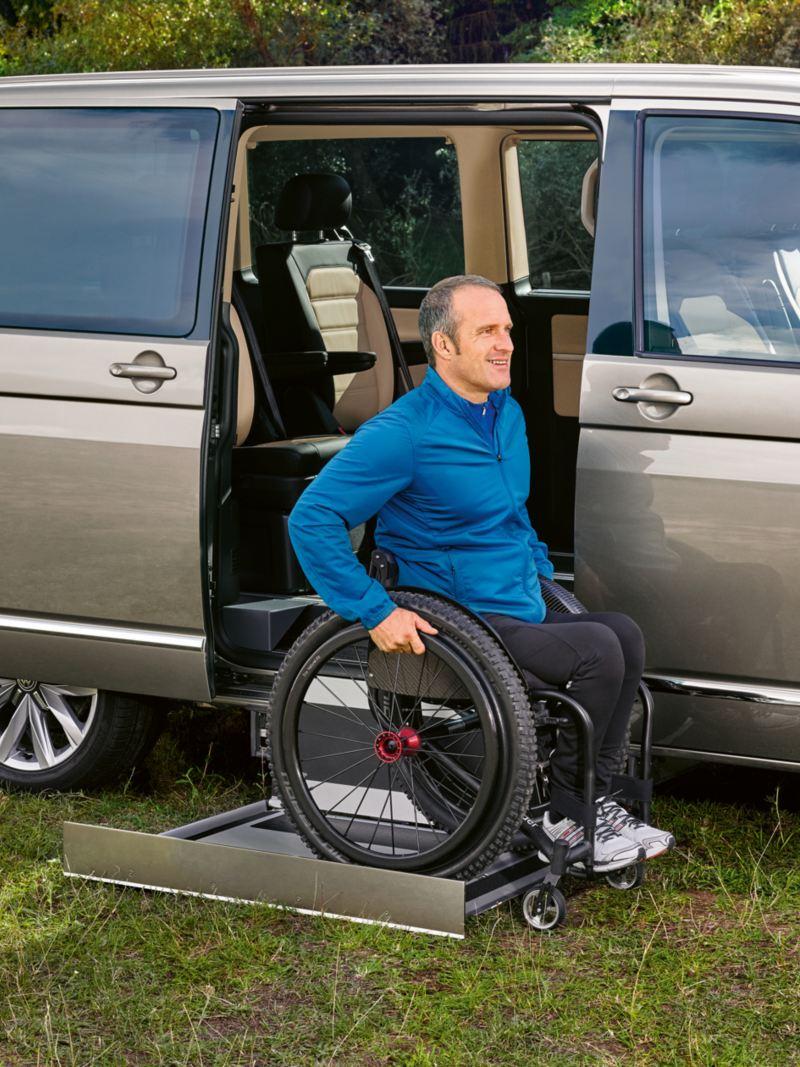 Ein Mann im Rollstuhl nutzt einen Kassettenlift, um in ein Fahrzeug einzusteigen.