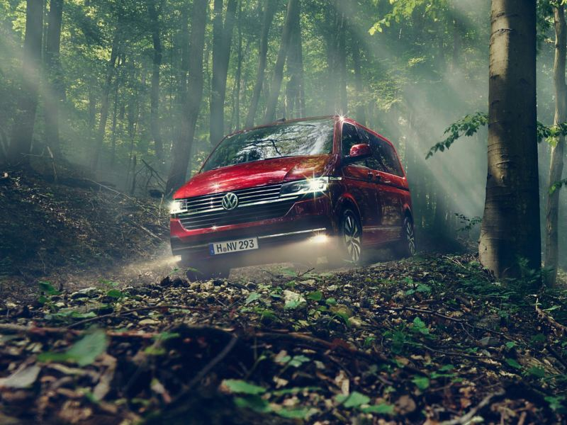 A red Multivan driving though a forrest.