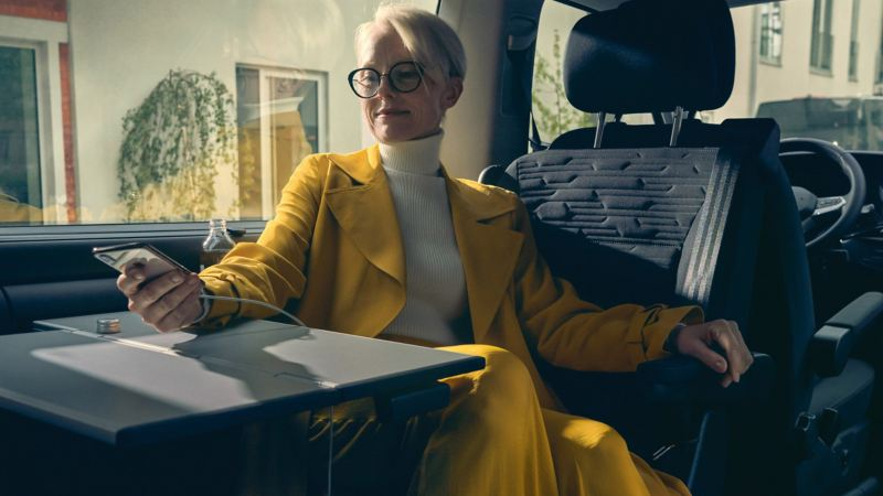 vw Volkswagen Multivan 6.1 Highline 7-seter familiebil minivan maxitaxi persontransport dame som surfer på smarttelefonen sin gul kåpe