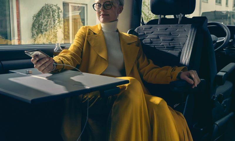 Eine Frau in gelben Mantel sitzt auf der Rückbank im Multivan 6.1 am Tisch und lädt ihr Handy.