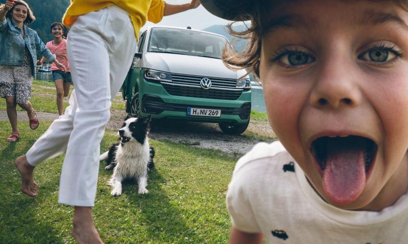 Ein Kind streckt der Kamera die Zungeraus. Im Hintergrund steht ein grün weißer Multivan und zwei Kinder und eine Frau rennen, ein Hund liegt auf dem Gras,