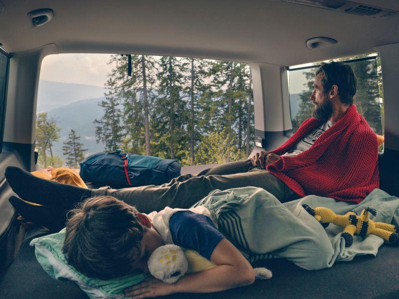 Ojciec i syn leżą na tylnym łóżku Volkswagena Multivan 6.1. Ojciec spogląda w dal, podczas gdy syn śpi.
