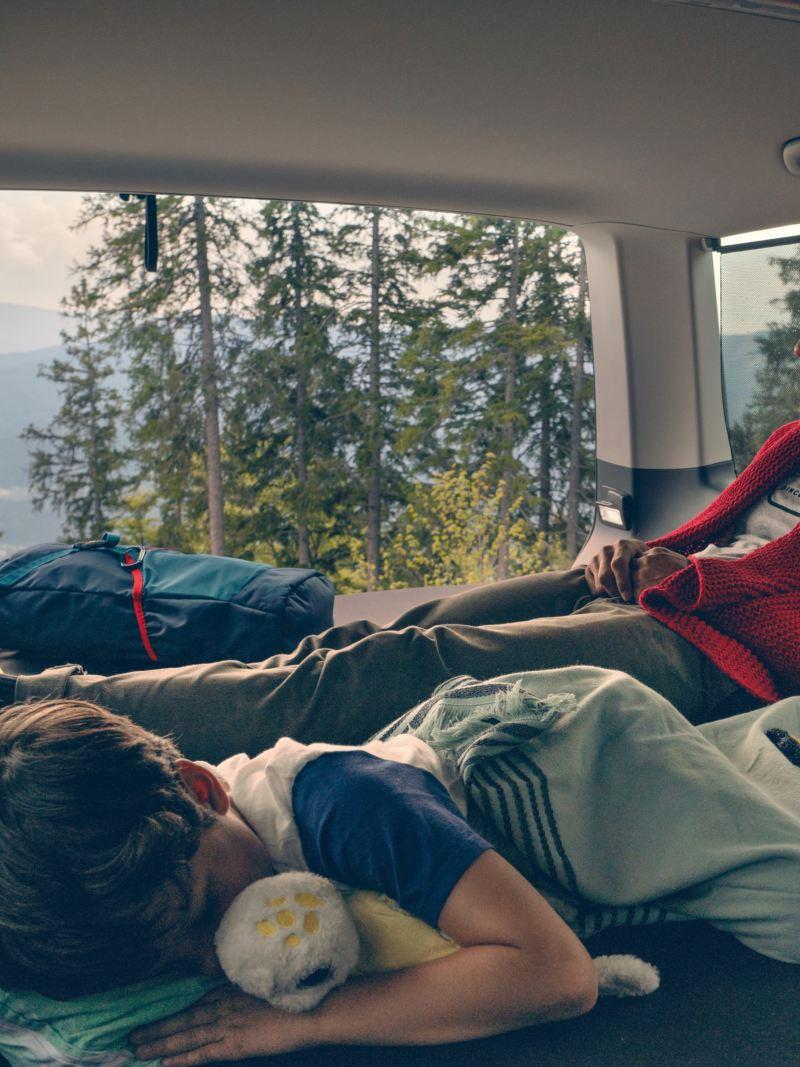Vater und Sohn liegen im Heckbett des Multivans 6.1. Der Vater guckt in die Ferne, während der Sohn schläft.
