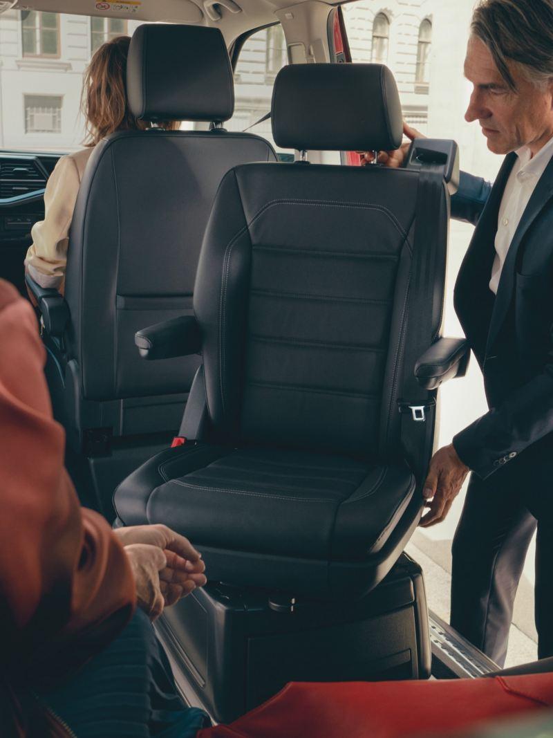 Mężczyzna obraca siedzenie w Volkswagenie Multivan 6.1. Pozostałe osoby siedzą na tylnym siedzeniu oraz siedzeniu pasażera..