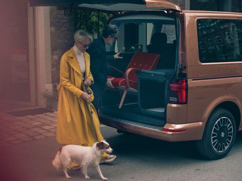 Mężczyzna ładuje krzesło do bagażnika Volkswagen Multivan 6.1.