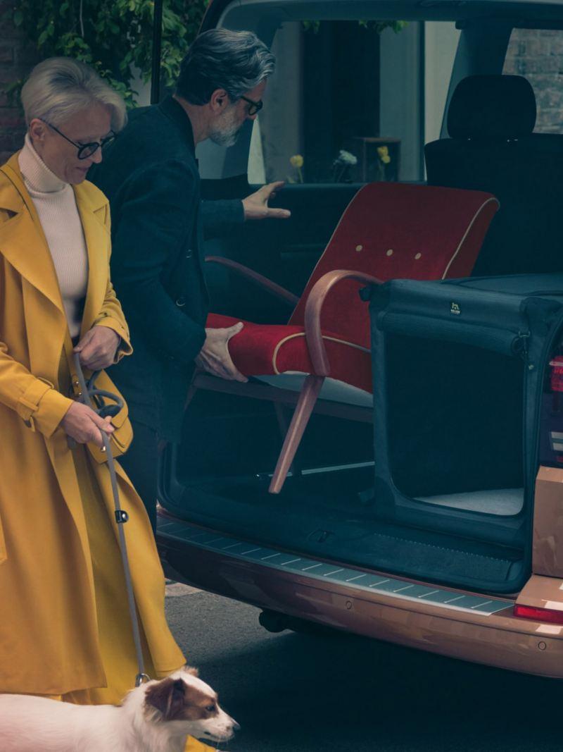 vw Volkswagen brun Multivan 6.1 Highline 7-seter familiebil minivan maxitaxi persontransport flyttebil flytte stol hund dame og mann laster inn i bagasjerommet