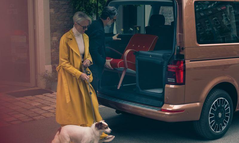 Ein Mann lädt einen Stuhl in den Kofferraum eines Multivan 6.1.