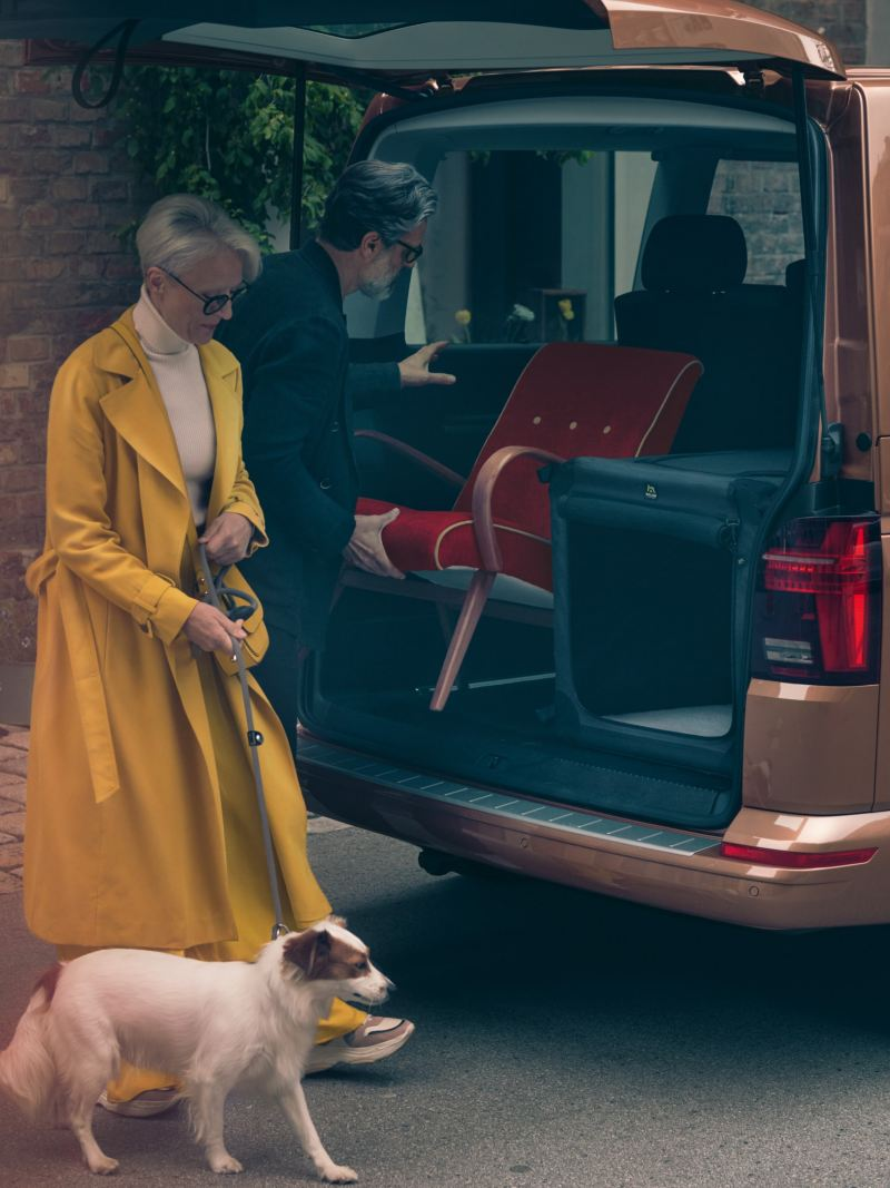 A man is loading a chair into the trunk of a Multivan. Next to him a woman dressed in yellow with a dog on a leash.