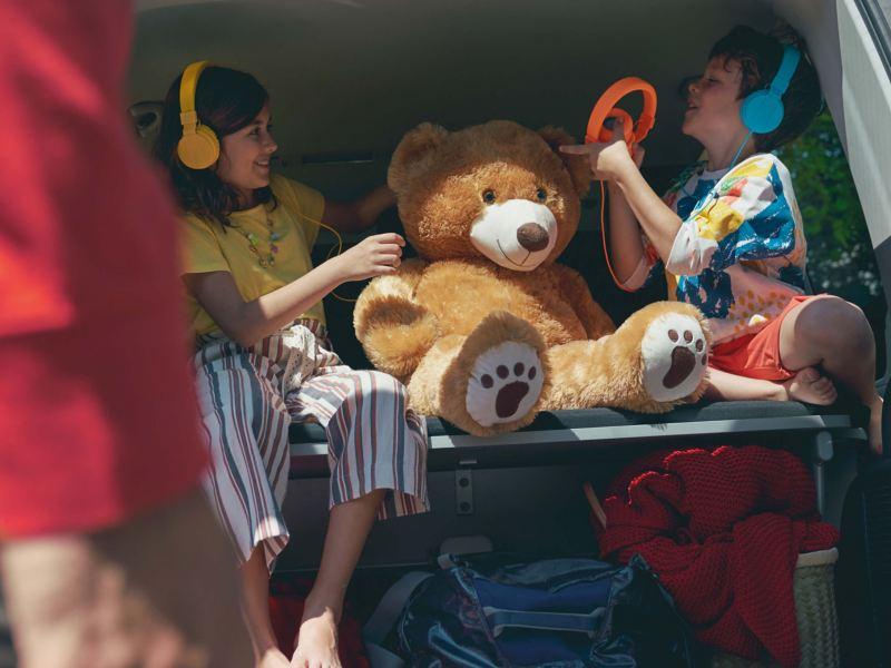 Duas crianças com os seus brinquedos estão sentadas atrás de uma carrinha Multivan 6.1.