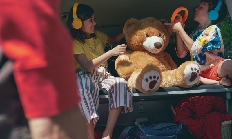 Zwei Kinder sitzen mit ihrem Spielzeug auf der klappbaren 3er-Sitzbank eines Multivan 6.1.