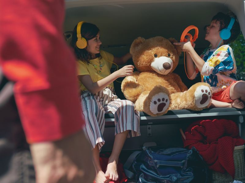Dwoje dzieci siedzi ze swoimi zabawkami na składanej 3-osobowej ławce Volkswagen Multivan 6.1.