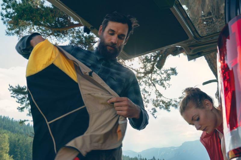 Un homme et une femme rangeant leurs affaires dans le coffre du Multivan 6.1
