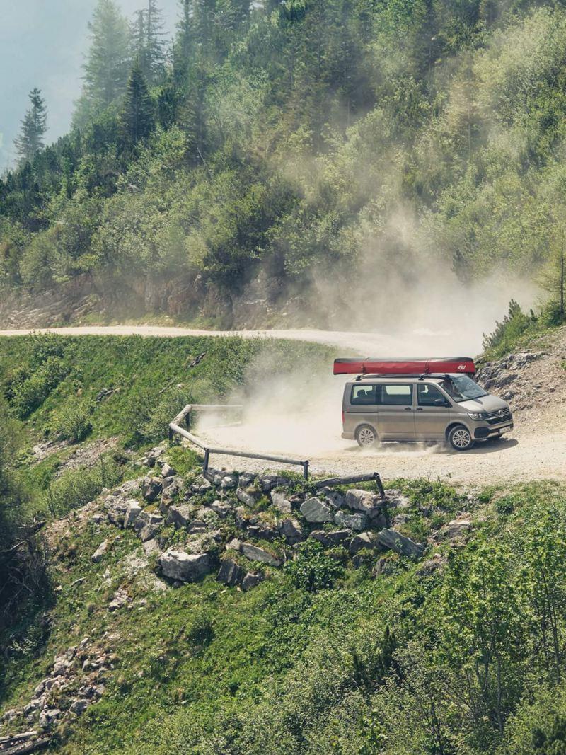 Ein Multivan fährt auf einen Bergweg.
