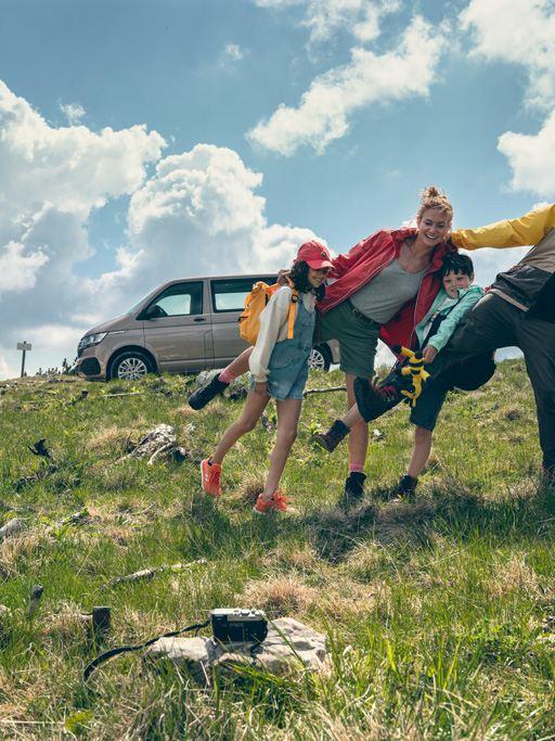 Une famille qui prennent une photo, heureux. A côté d'eux, un Multivan 6.1 gris.