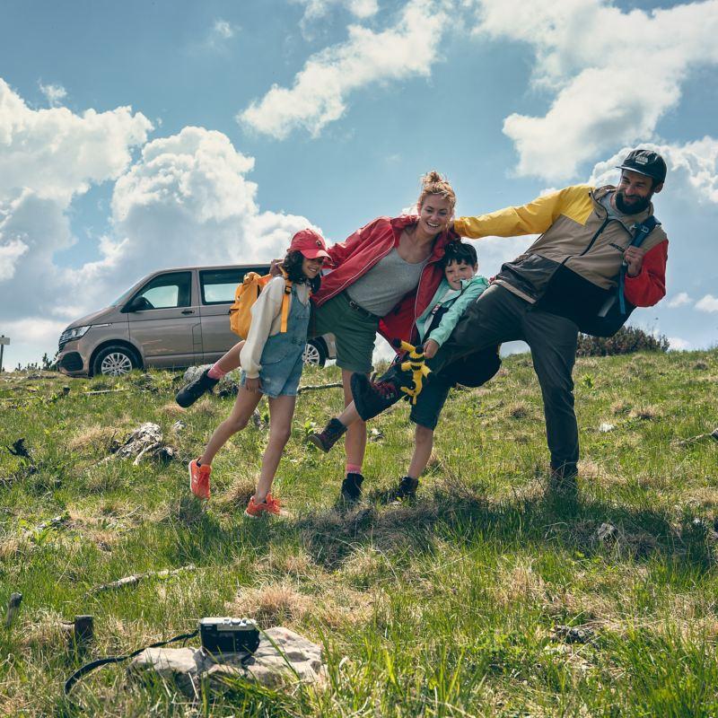 Eine Familie fotografiert sich vor einem Volkswagen Multivan 6.1.