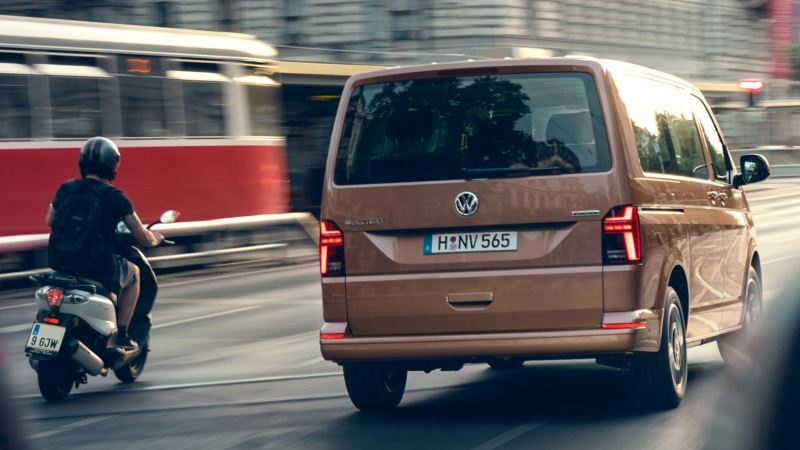 vw Volkswagen beige Multivan 6.1 Highline 7-seter familiebil minivan maxitaxi persontransport kjører i trafikken BlueMotion technology scooter trikk bysenter