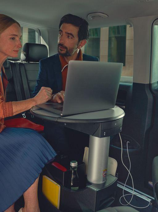 un homme et une femme assis dans le Multivan 6.1 regardant un ordinateur.