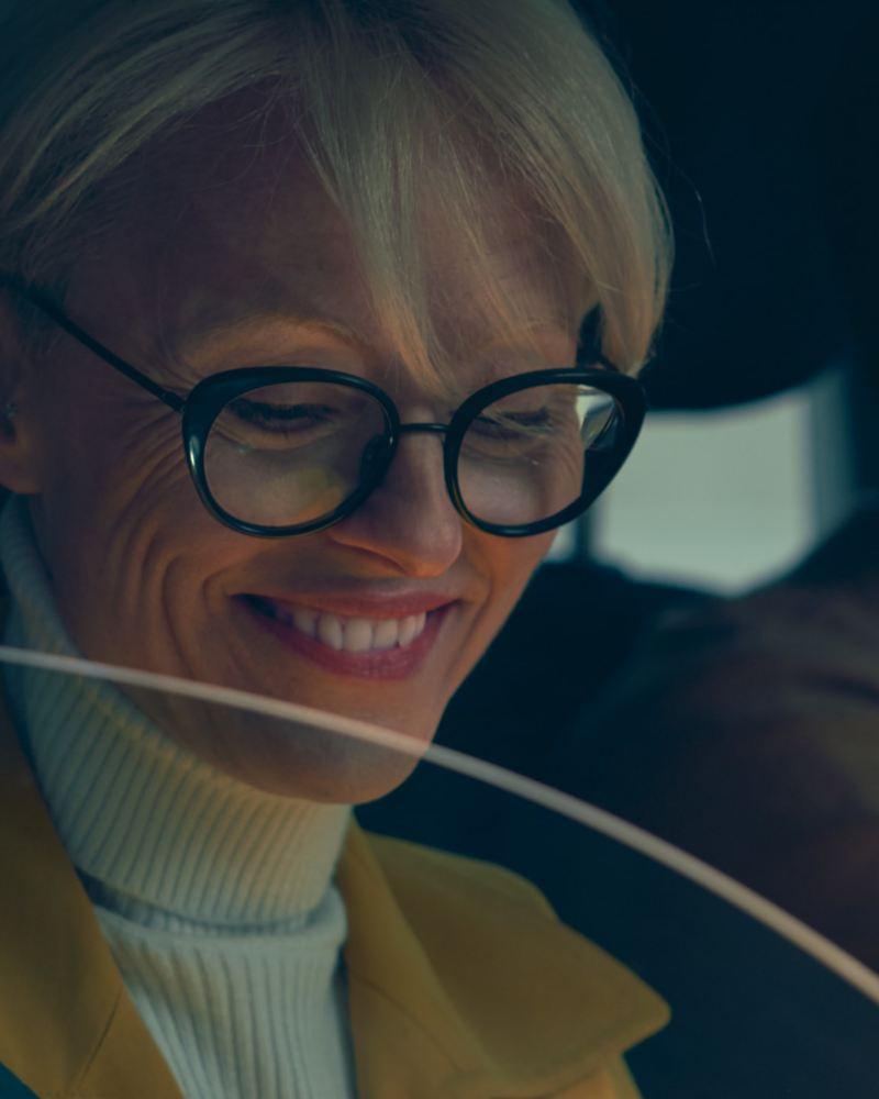 Eine Frau sitzt auf dem Beifahrersitz und blickt lachend nach unten
