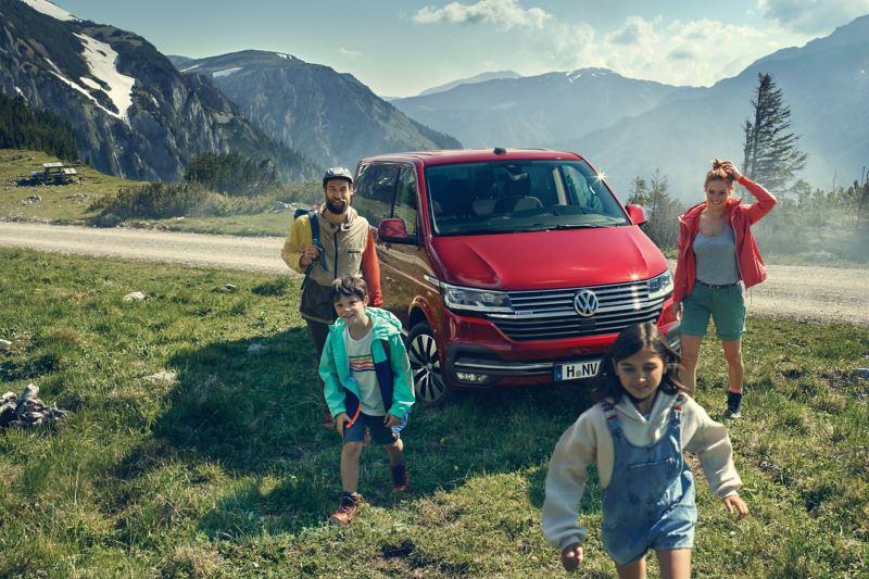 En röd VW Multivan minibuss med en familj