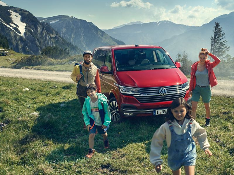 Eine Familie bewegen sich auf die Kamera zu. Neben ihnen ein roter Multivan 6.1.