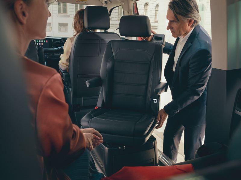 Ein Mann dreht einen Sitz der Rückbank. Weitere Personen sitzen auf den Beifahrersitz und auf der Rückbank.