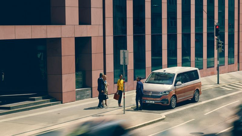 Der Multivan 6.1 Generation Six von Volkswagen Nutzfahrzeuge in der Lackierung Candy-Weiß/Copper Bronze steht am Straßenrand.