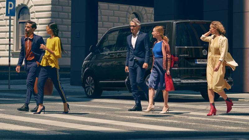 Ein Volkswagen Multivan 6.1 Exclusive fährt durch eine urbane Szenerie.