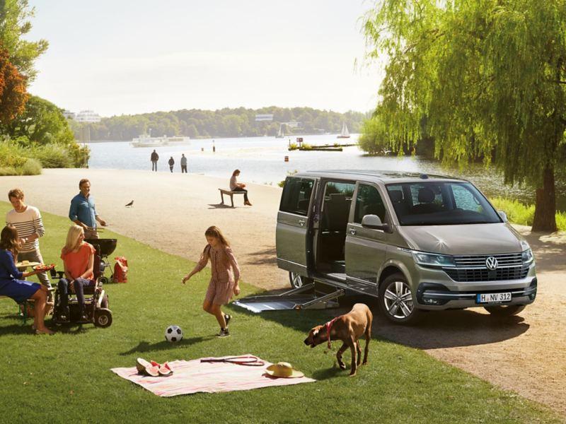 Eine Familie mit Rollstuhlfahrerin im Park neben ihrem umgebauten VW Multivan 6.1.