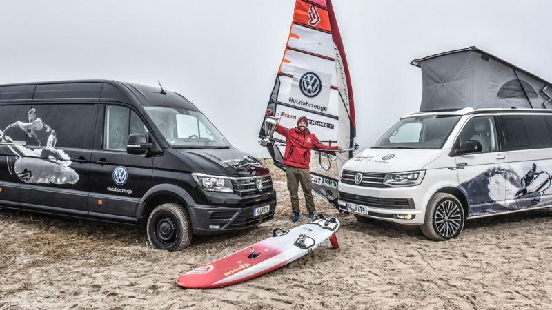 Vincent Langer steht mit seinem Windsurf-Board zwischen zwei Multivans am Strand.